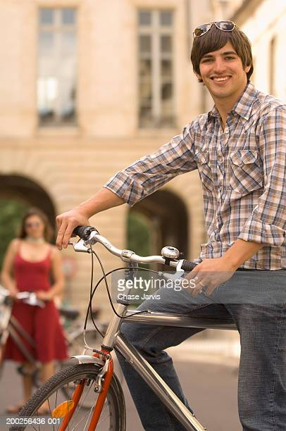young man and woman riding bicycles (focus on man in foreground) - lebanese ethnicity stock photos and pictures