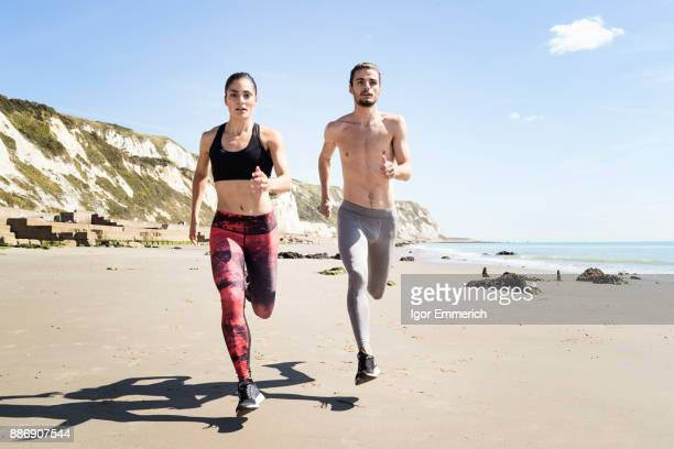 Young man and woman running along beach, front view