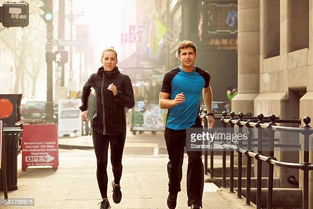 Young man and woman running along street, Pioneer Square, Seattle, USA