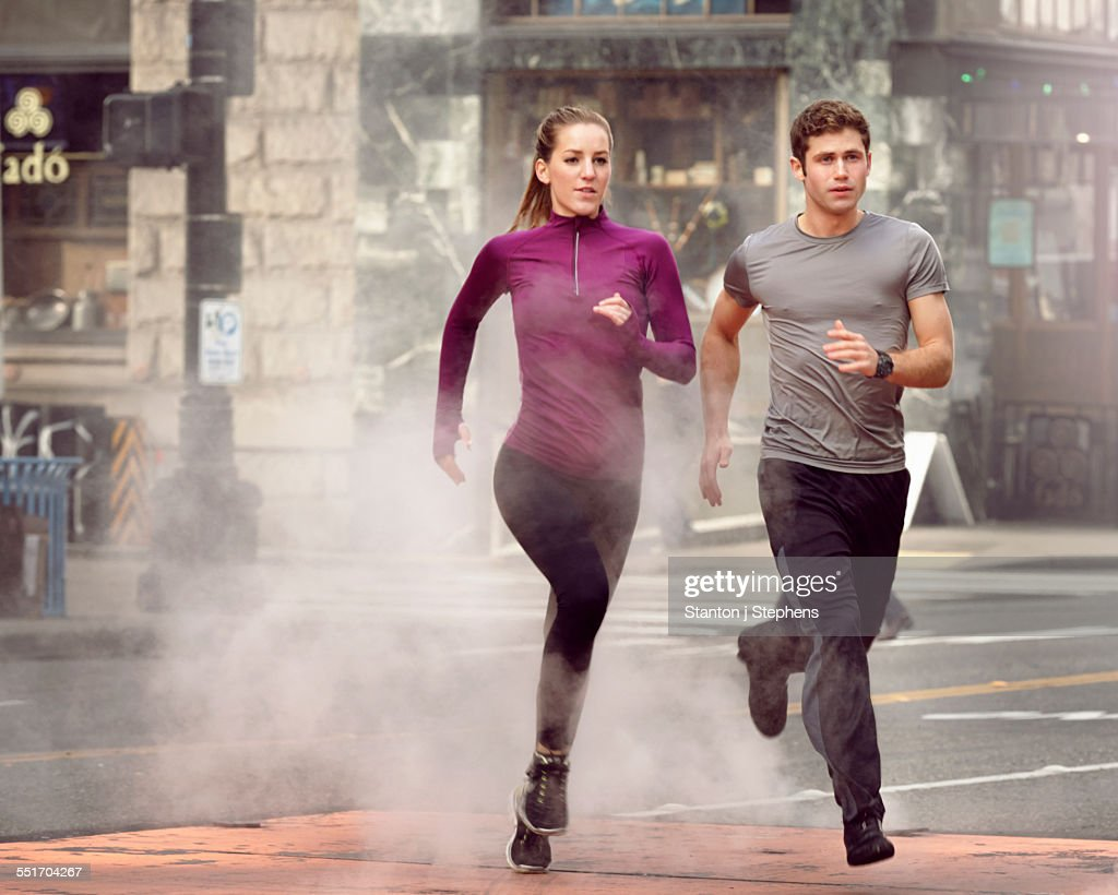 Young man and woman running through steam, Pioneer Square, Seattle, USA : Foto stock