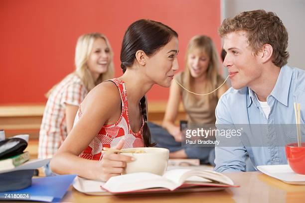 giovane uomo e donna nella caffetteria condivisione di pasta - noodle foto e immagini stock