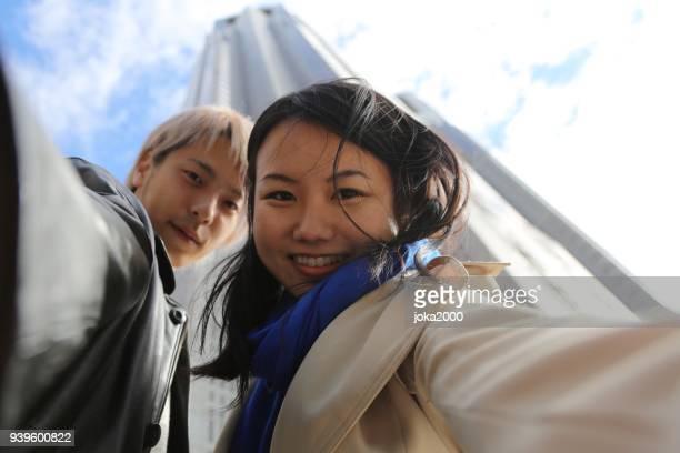 若い男と女の背の高いビルの前で selfies を撮影