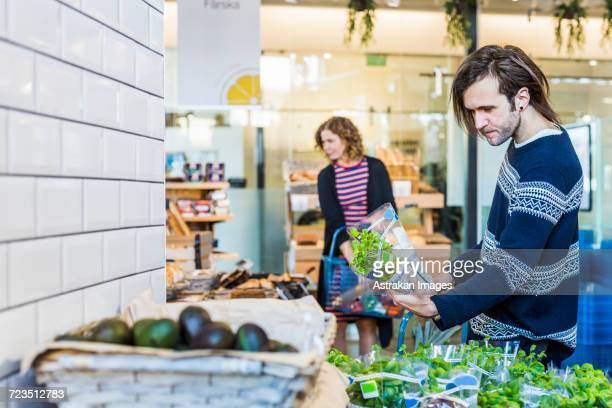 Young man and woman shopping in supermarket