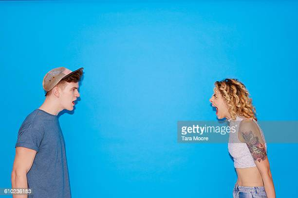 young man and woman shouting at each other - shouting stock pictures, royalty-free photos & images