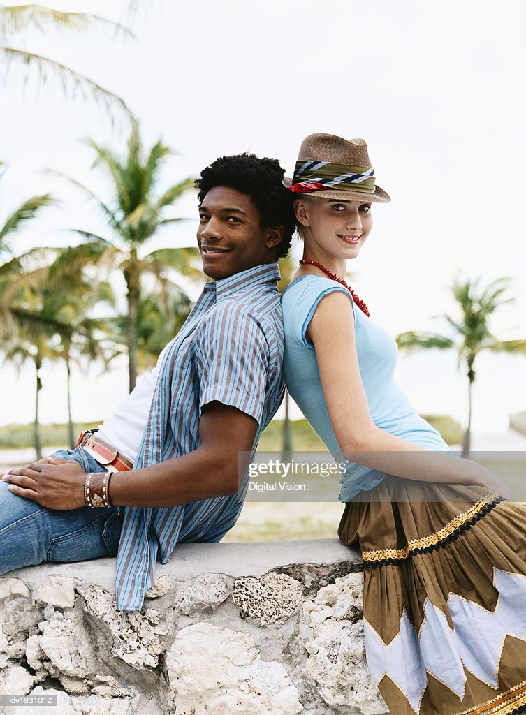 Young Man and Woman Sit Back to Back on a Stone Wall, Leaning on Each Other : Stock Photo