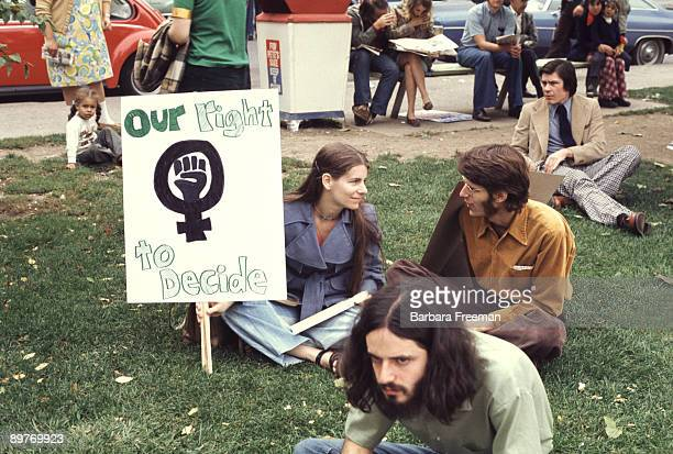 A young man and woman sit on the grass holding a sign that reads 'Our Right To Decide' at a reproductive rights demonstration Pittsburgh PA 1974