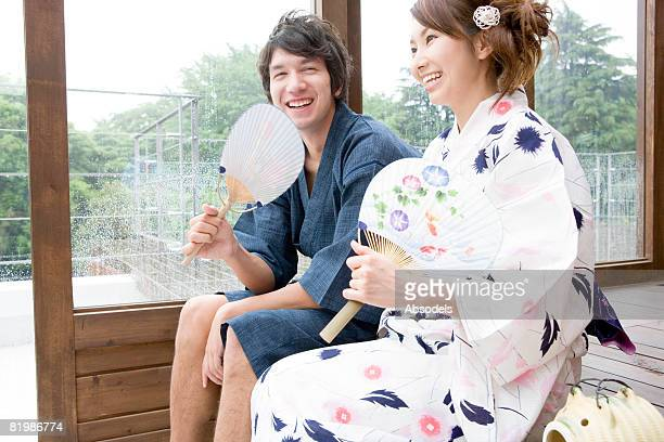 Young man and woman sitting and holding fun near window, smiling