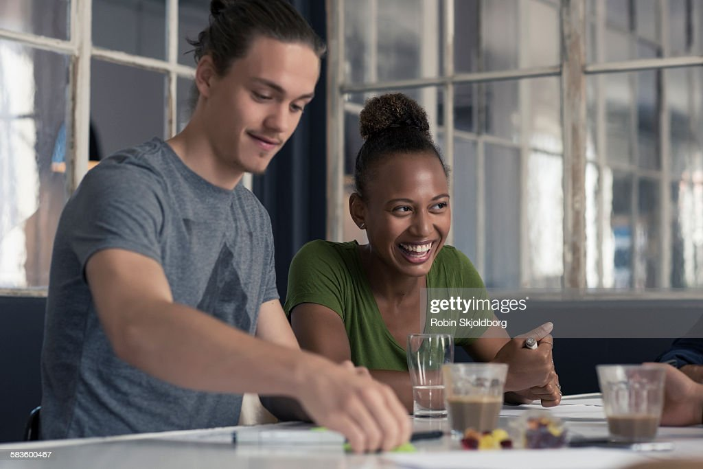 Young Man and Woman sitting at table laughing : Stock Photo