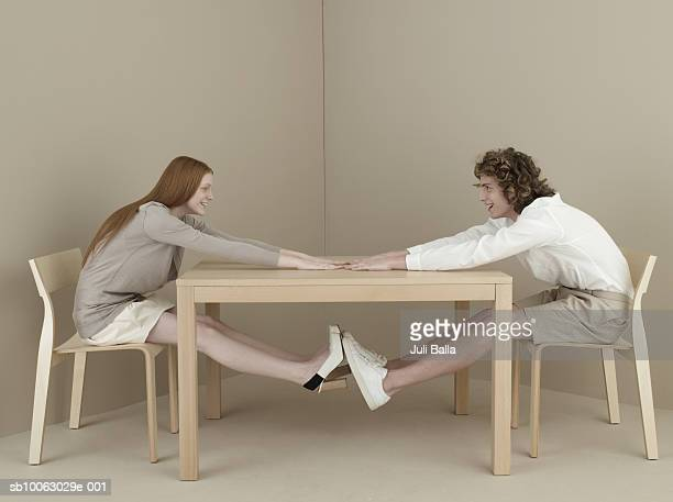 Young man and woman sitting at table stretching, side view