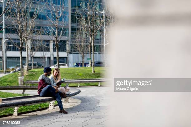 Young man and woman sitting on bench, studying, using digital tablet and laptop