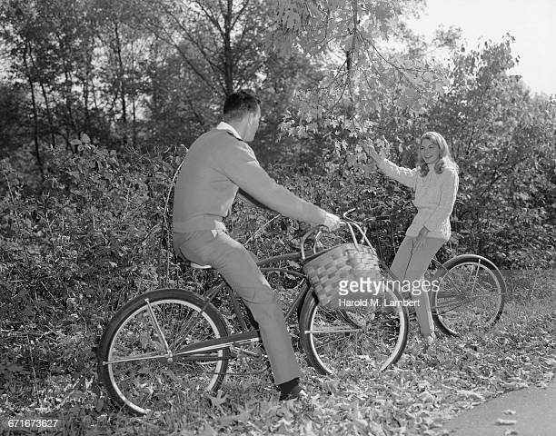 young man and woman sitting on bicycle - {{ collectponotification.cta }} foto e immagini stock