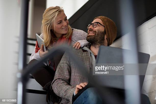 Young man and woman sitting on stairs using laptop