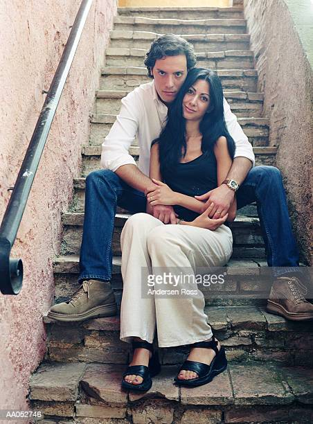 Young man and woman sitting on stairway, embracing, portrait