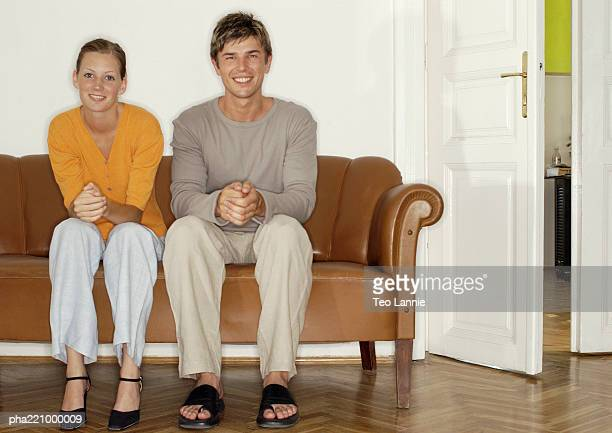 Young man and woman sitting side by side on sofa, off center