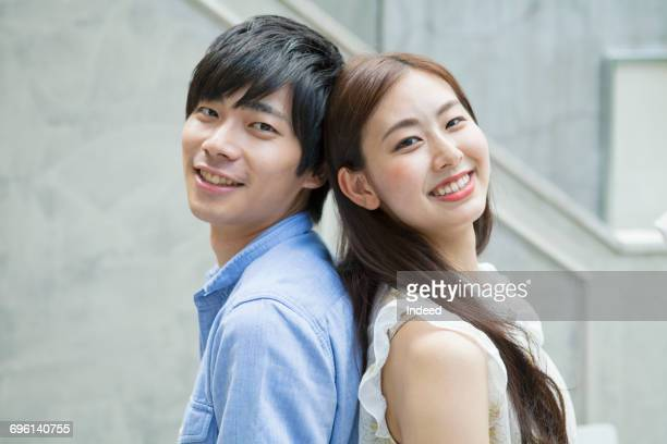 young man and woman smiling back to back - 背中合わせ ストックフォトと画像