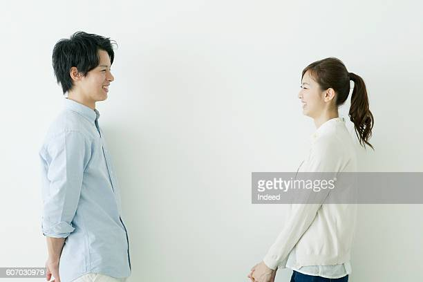 Young man and woman smiling face to face