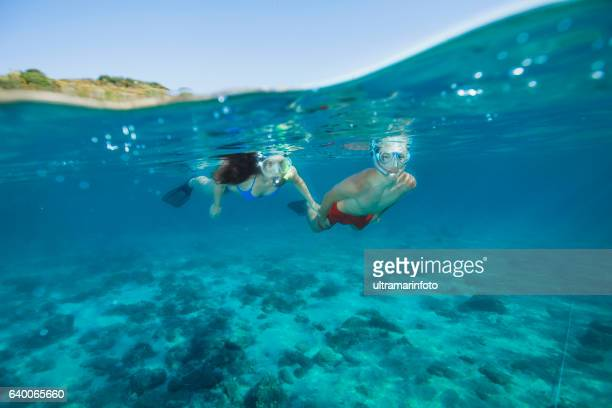 Young man and woman snorkeling  Underwater diving adventure  Turquoise sea