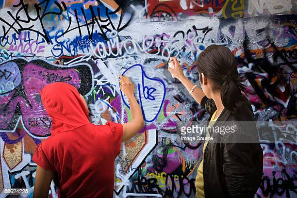 A young man and woman spraying graffiti