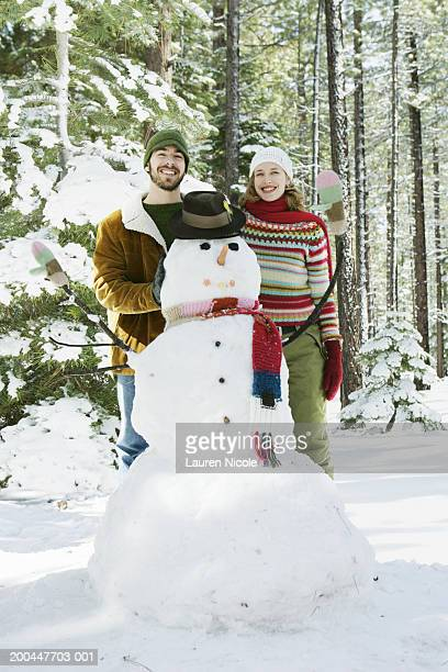 Young man and woman standing behind snowman, smiling, portrait