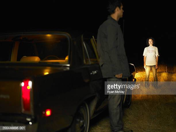 Young man and woman standing beside car, night (focus on woman)