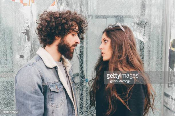 young man and woman, standing face to face, pensive expressions - couple arguing stock photos and pictures