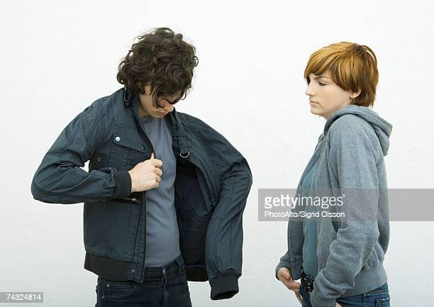 Young man and woman standing, man putting on jacket while woman watches