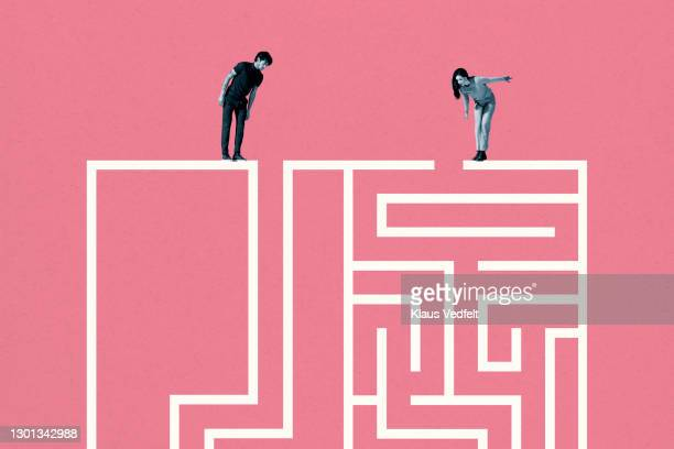 young man and woman standing on top of white maze - direction stock pictures, royalty-free photos & images