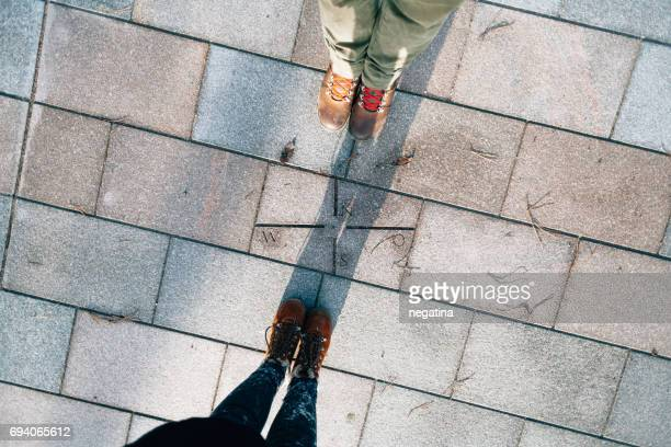 young man and woman standing over engraved compas on the tiled floor