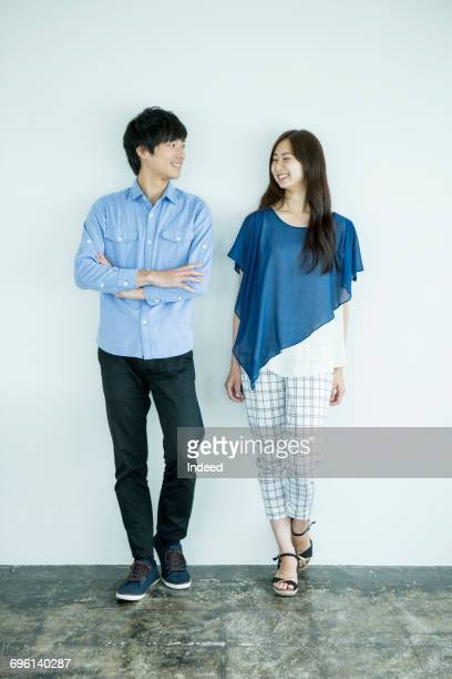 young man and woman standing, smiling face to face - two people ストックフォトと画像