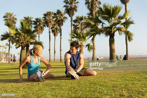 Young Man and Woman Stretch before Running at Beach