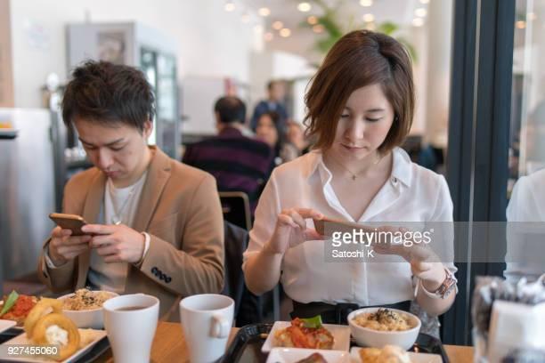 若い男と女の個別食品のランチの写真を撮る - 昼食 ストックフォトと画像