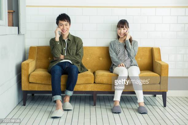 young man and woman talking on smart phone - 座る ストックフォトと画像