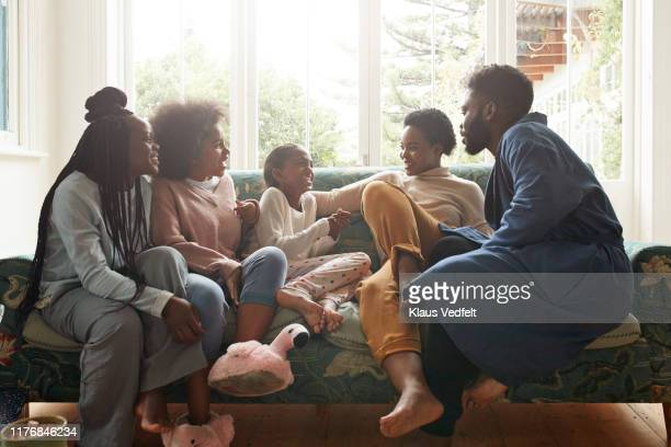 Young man and woman talking with children at home