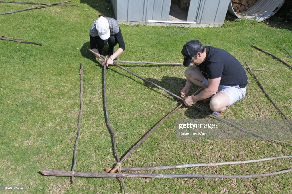 Young Man and Woman Tying Knots Pieces of Wooden Poles : Stock Photo