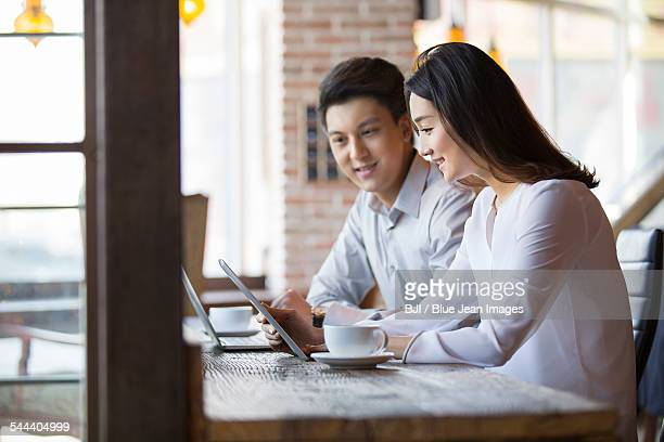 Young man and woman using digital tablet in cafe