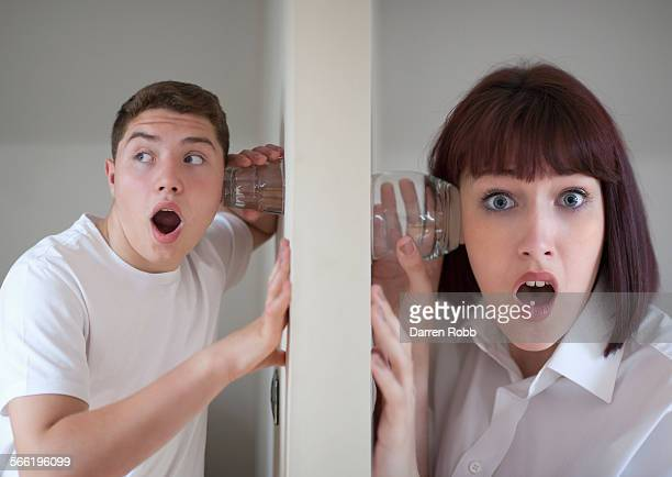 Young man and woman using glasses to eavesdrop