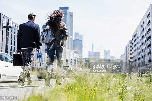young man and woman walking in the city - gemeinsam gehen stock-fotos und bilder