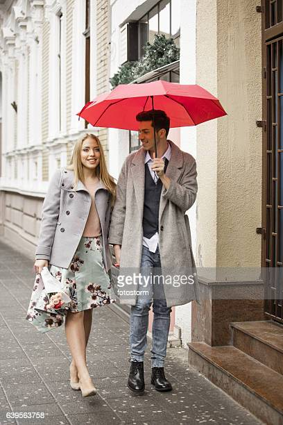 Young man and woman walking on pedestrian on rainy day