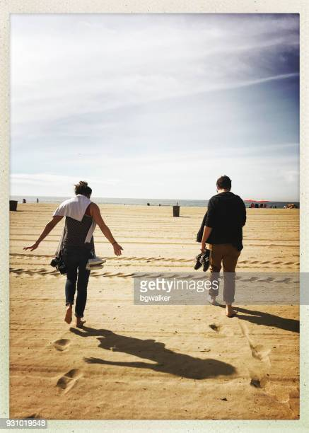 Young Man and Woman Walking towards Pacific Ocean