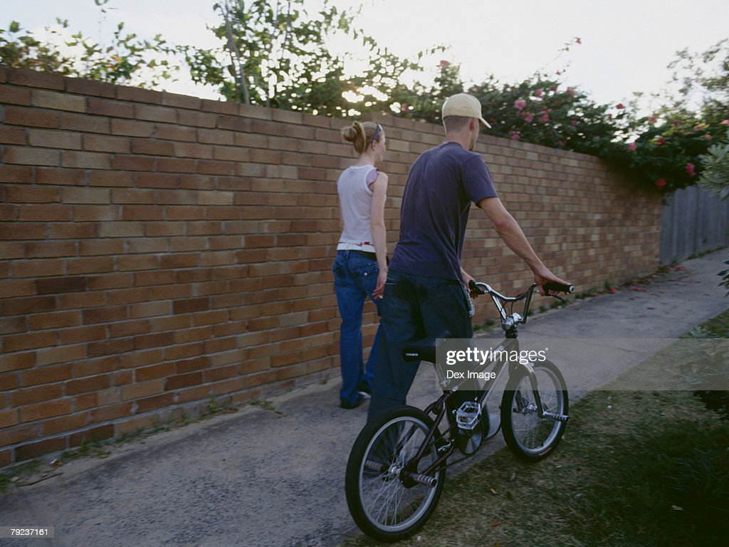 Young man and woman walking with bike, rear view : Stock Photo