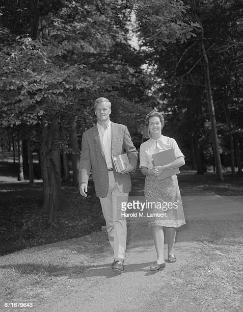 young man and woman walking with book - {{relatedsearchurl(carousel.phrase)}} ストックフォトと画像