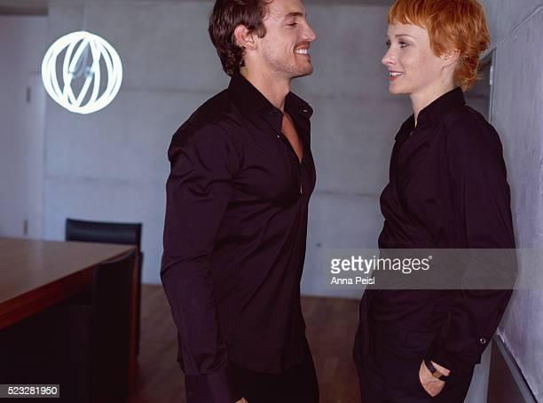 young man and woman wearing black shirts talking - 黒のシャツ ストックフォトと画像