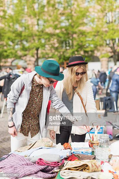 Young man and woman wearing sunglasses shopping at flea market