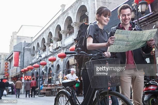 young man and woman with bicycle and map. - beijing stock pictures, royalty-free photos & images