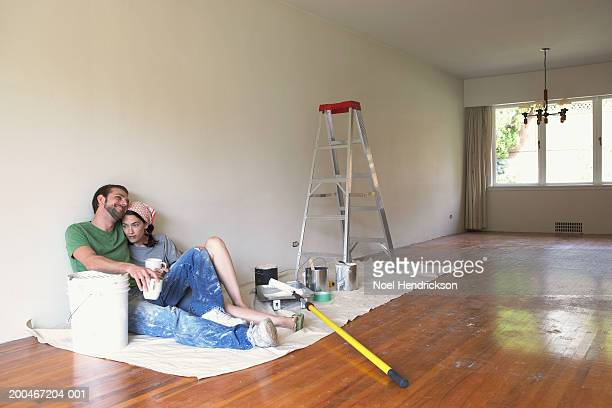 Young man and woman with mugs sitting on floor beside bucket of paint