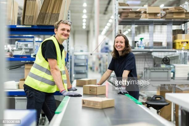 junger mann und frau arbeiten im lager - fließbandfertigung stock-fotos und bilder