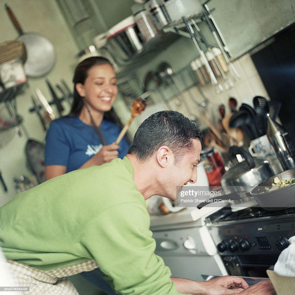 Young man and woman working together in kitchen, focus on foreground, man bending toward oven. : Stock Photo