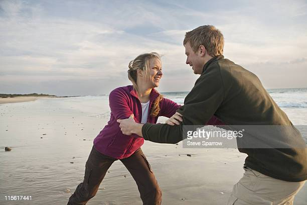 Young man and woman wrestling at beach
