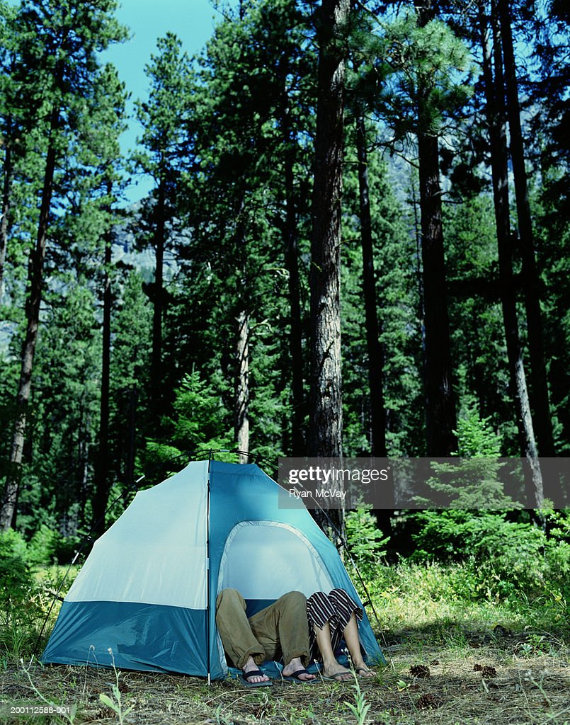 Young man and woman's legs sticking out of tent : Stock Photo