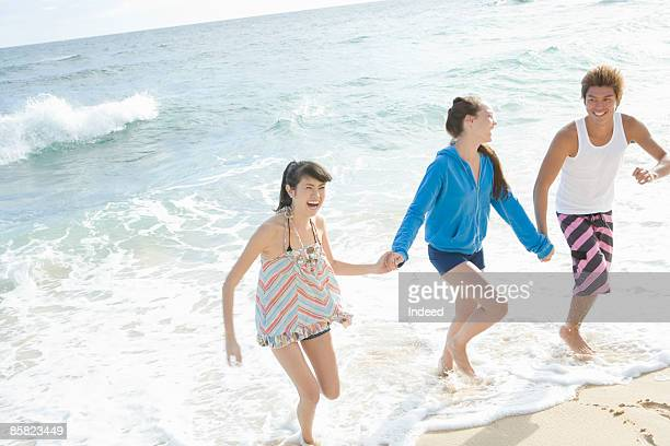 young man and women holding hands and running - ragazzine scalze foto e immagini stock